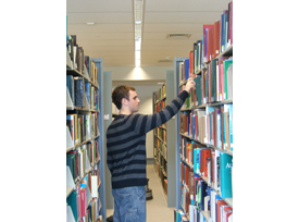 Student finds book on one of the shelves on the first floor of the library
